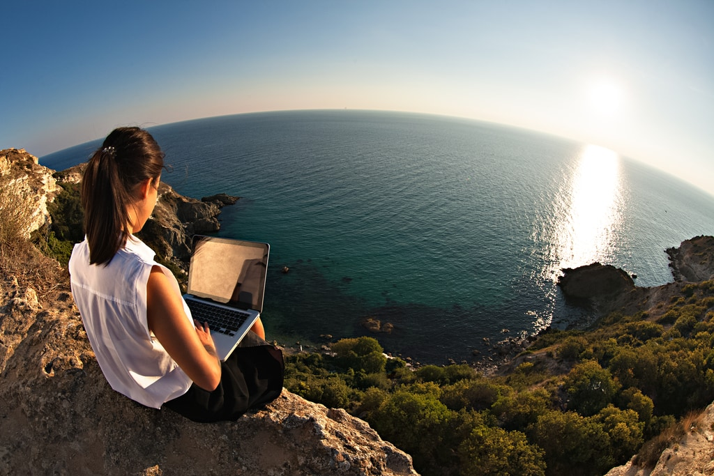 successful woman with laptop sitting over lake